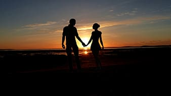 Silhouette of couple holding hands on beach during sunset