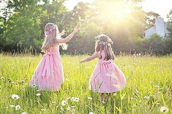 Girl in pink dress standing on green grass field during daytime