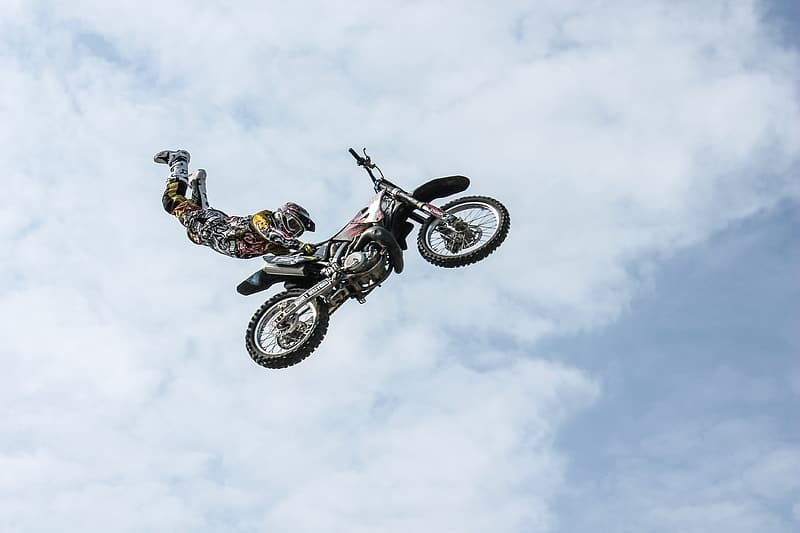 Man wearing motocross gear doing superman stunt in mid air