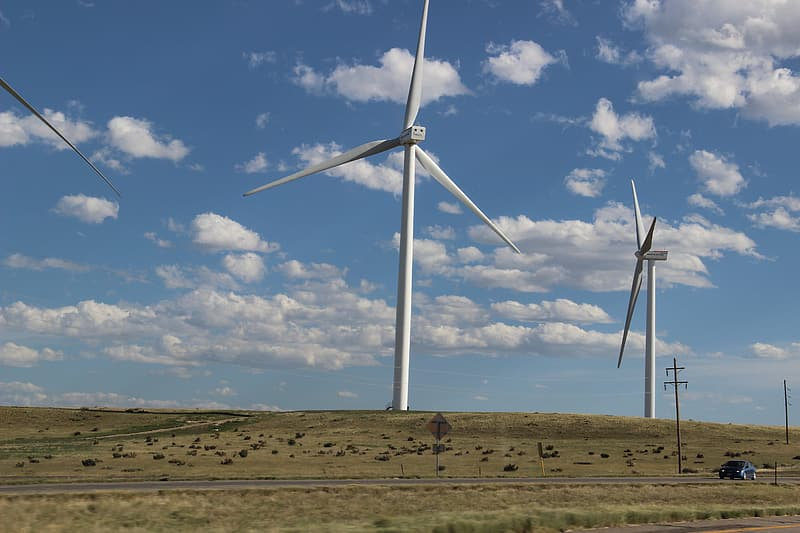 White wind turbines on brown field under blue and white cloudy sky during daytime