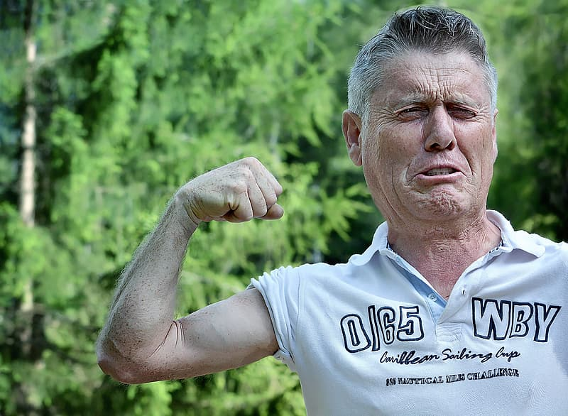 Man in white polo shirt showing right bicep