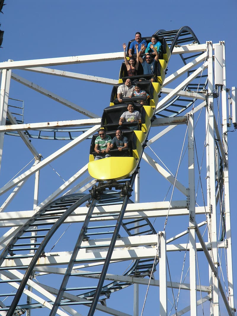 Group of people riding roller coaster during daytime