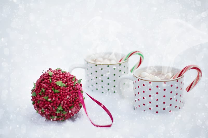 Two white-and-red polka-dot mugs filled with marshmallows