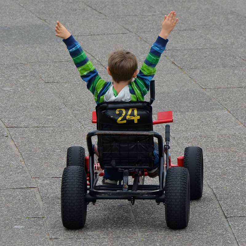 Girl in blue and yellow jacket riding on red and black go kart on gray concrete