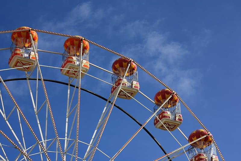People riding on white and brown ferris wheel under blue sky during daytime