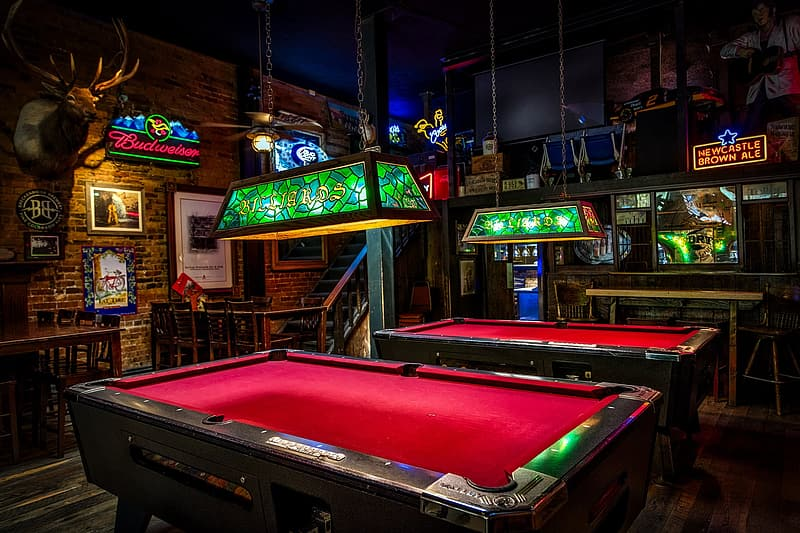 Two red-and-brown pool tables inside the room beside brown wooden desk