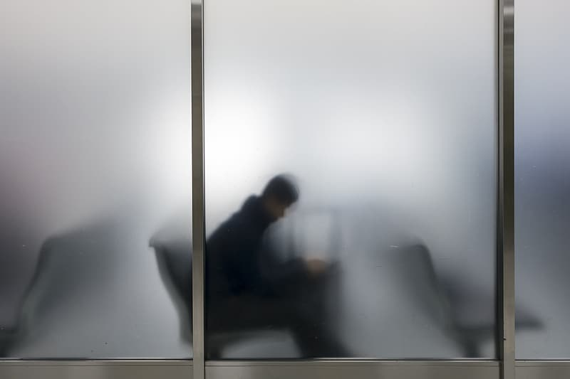 Silhouette of man behind frosted glass window