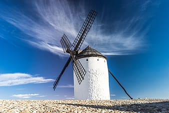 White lighthouse with black windmill under white clouds photography