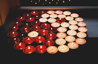 White and red candles on black surface