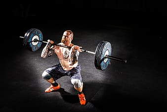 Man wearing a black short while lifting a black steel barbell