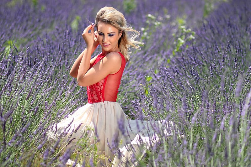 Woman in red sleeveless top and white skirt sitting in lavender field