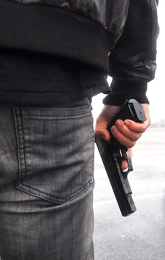 Person wearing black leather jacket holding black semi-automatic