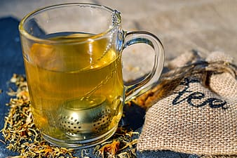 Yellow liquid filled clear glass mug beside gray drawstring pouch