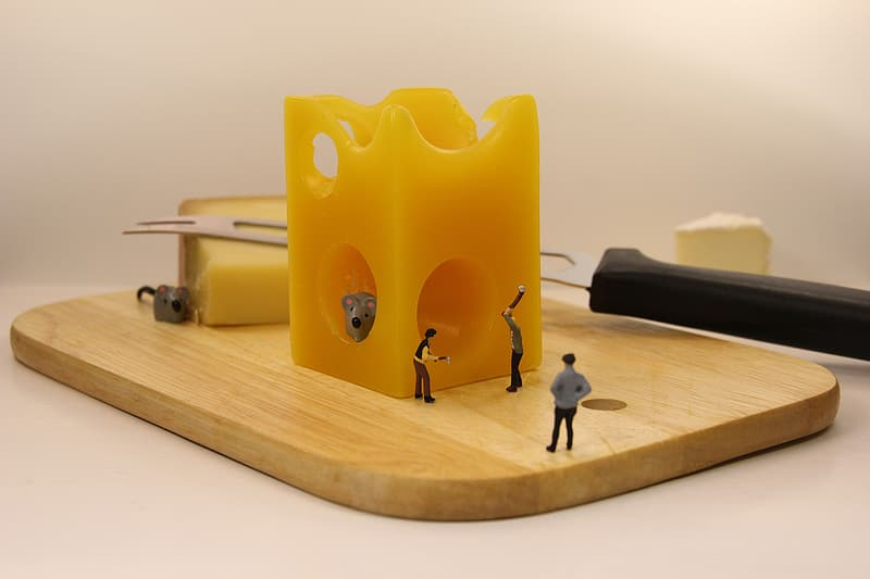 Working people figurines on chopping board with cheese