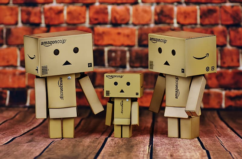 Three brown Amazon cardboard human-designed boxes standing on brown surface near brick wall