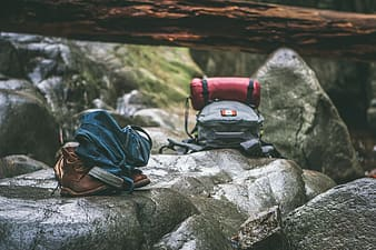 Blue and black backpack on gray rock