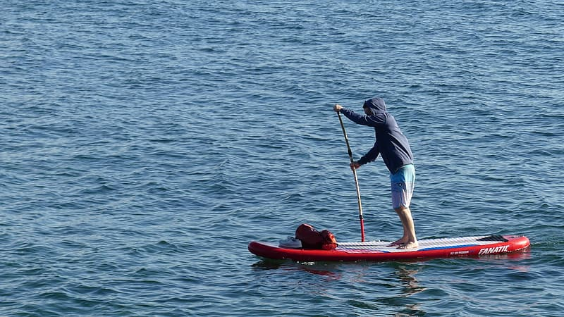 Man in blue shirt and blue shorts riding red kayak on sea during daytime