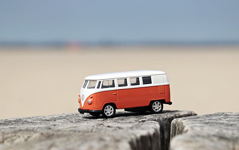 Shallow focus photography of white and red Volkswagen Samba die-cast toy car