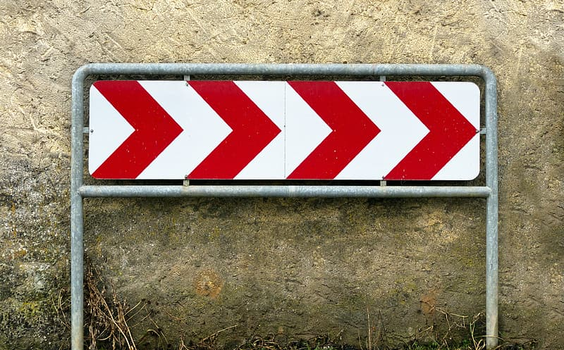 Red and white arrow signage beside wall