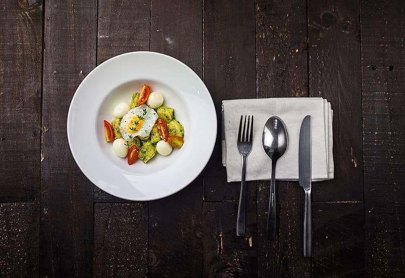 Fried egg with greens on round white ceramic plate beside spoon, fork, and knife on top of white linen