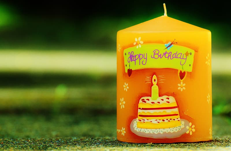 Selective photography of yellow Happy Birthday pillar candle