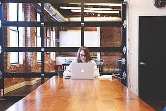 Woman in white long-sleeved shirt using MacBook