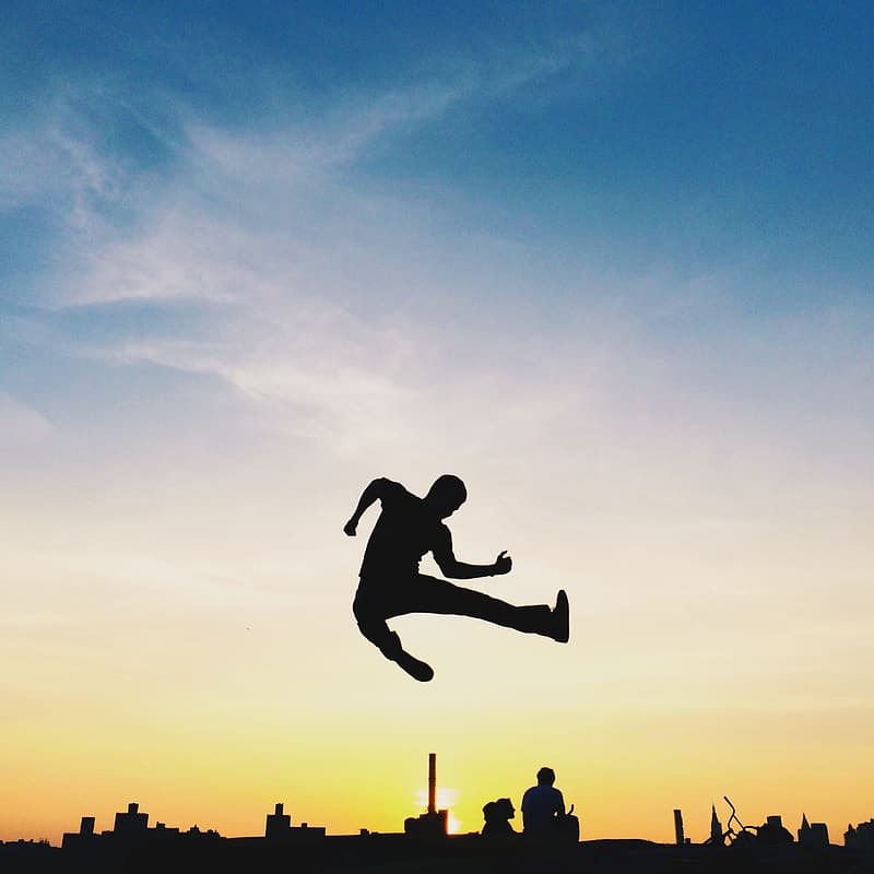 Silhouette of man jumping near cityscape