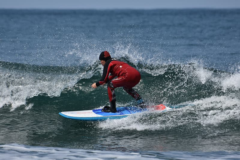 Man in red wet suit riding blue surfboard on sea waves during daytime