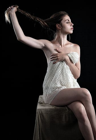 Photo of woman holding her hair while cover her body sitting on square wooden stool
