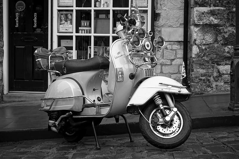 Grayscale photo of motor scooter parked near house