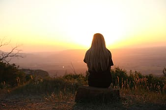Woman sitting on rock facing golden hour