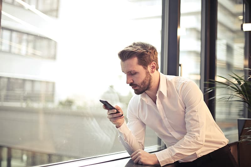 Young Adult Man in White Shirt Checking His Phone Near Window In Office