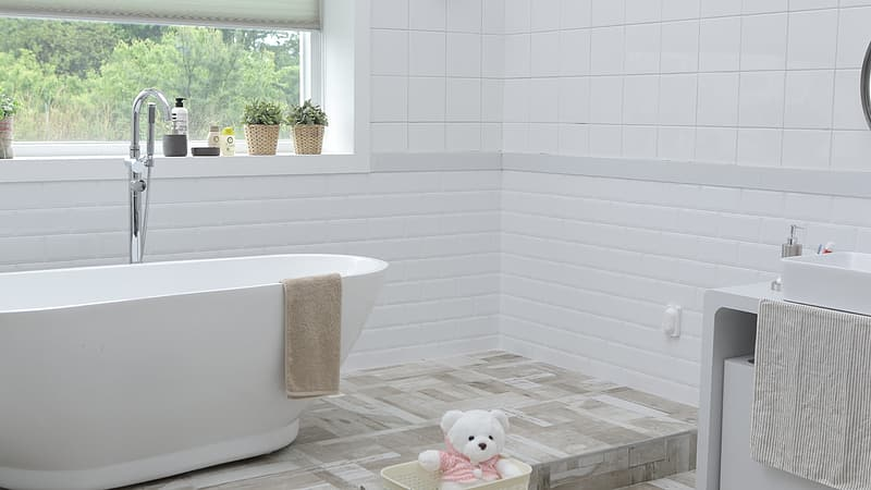 White ceramic tub with stainless steel faucet during day time