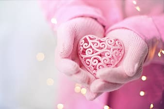 Person holding silver and pink heart ring