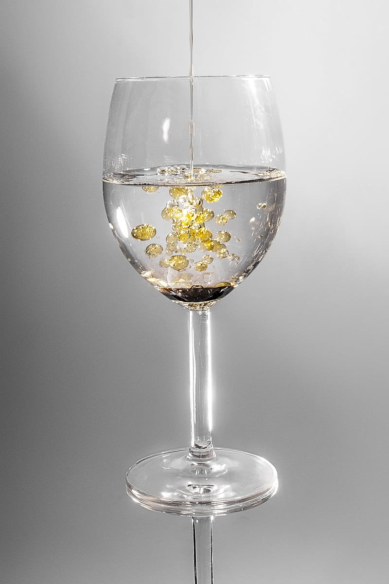 Clear wine glass filled with clear and yellow liquid