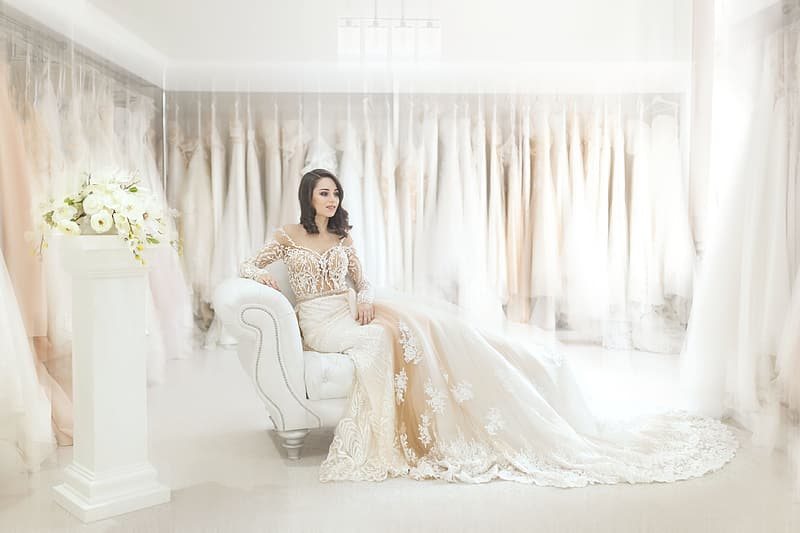 Woman in white floral dress sitting on white sofa chair