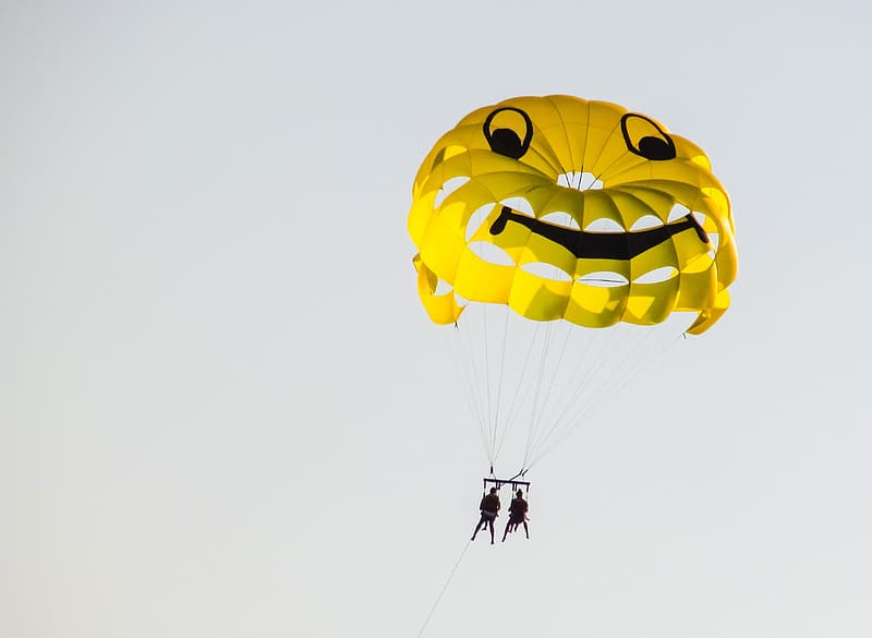 Person in black jacket and black pants with yellow and blue parachute in the sky