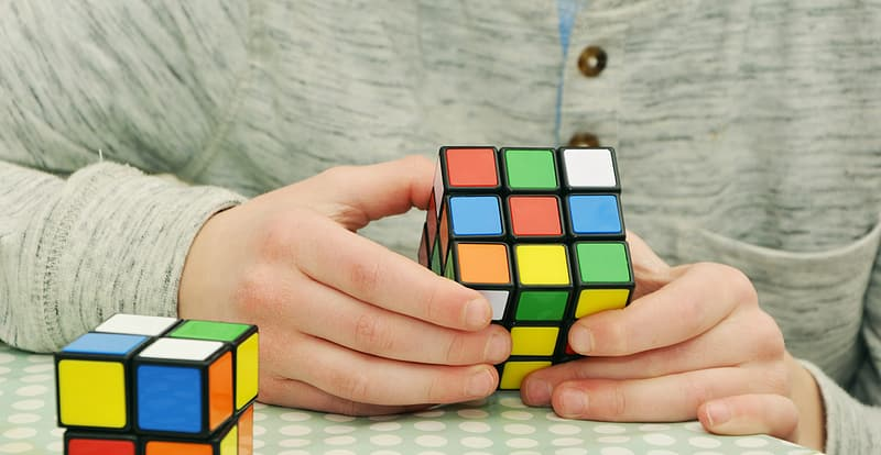 Person holding 3 by 3 Rubik's cube