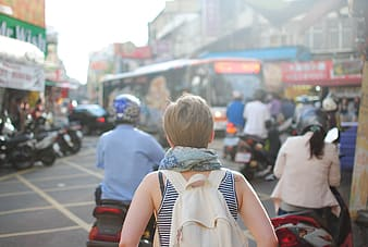 Woman facing back with beige backpack standing beside motorcycle