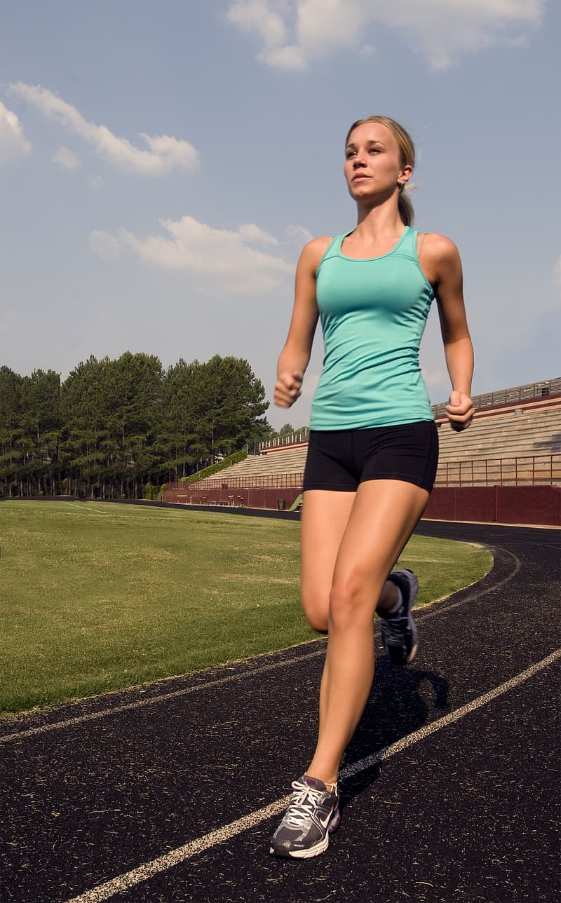 Woman wearing teal tank top running in the track field