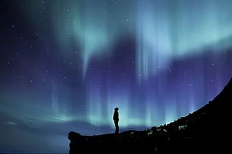 Person standing in mountain viewing Aurora