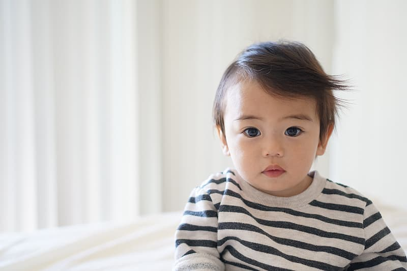 Toddler poses wearing black and gray striped crew-neck shirt