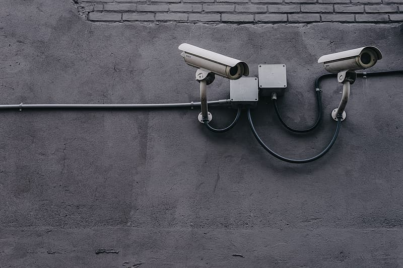 Two white CCTV cameras on gray wall