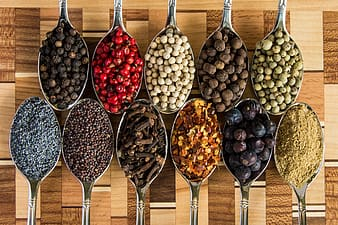 Brown and black beans on stainless steel spoons
