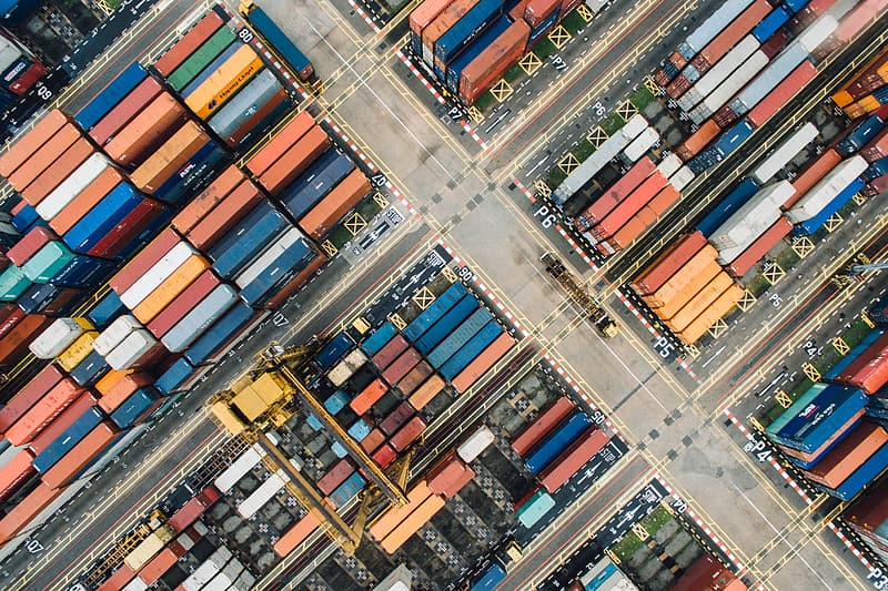 Bird's-eye view of piled intermodal containers on concrete ground