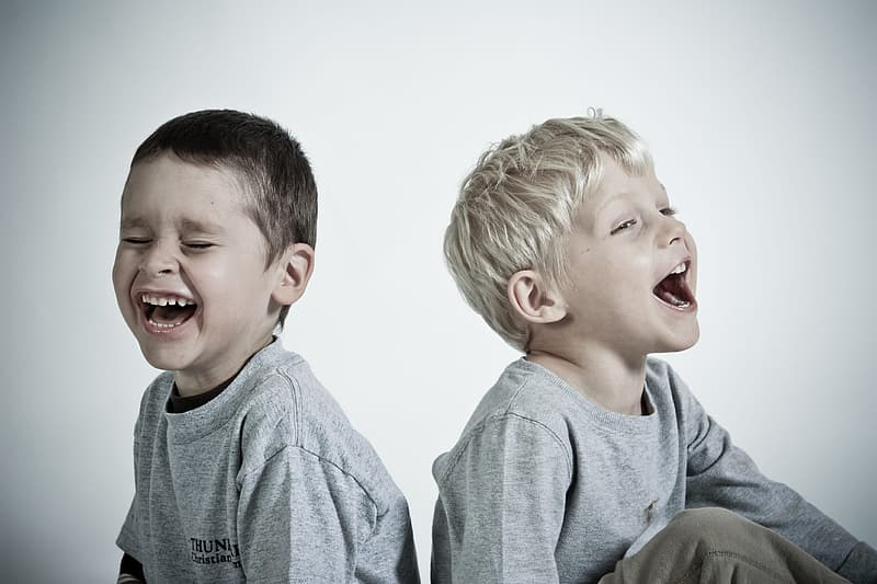 Photography of two children wearing heather gray shirts while laughing