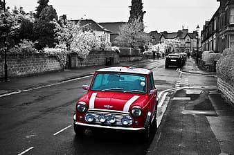 Selective color photo of red Mini Cooper parked on the side of the road