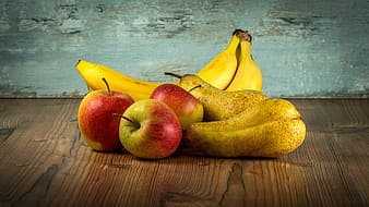 Two bananas and three ripe apples on top of brown wooden surface