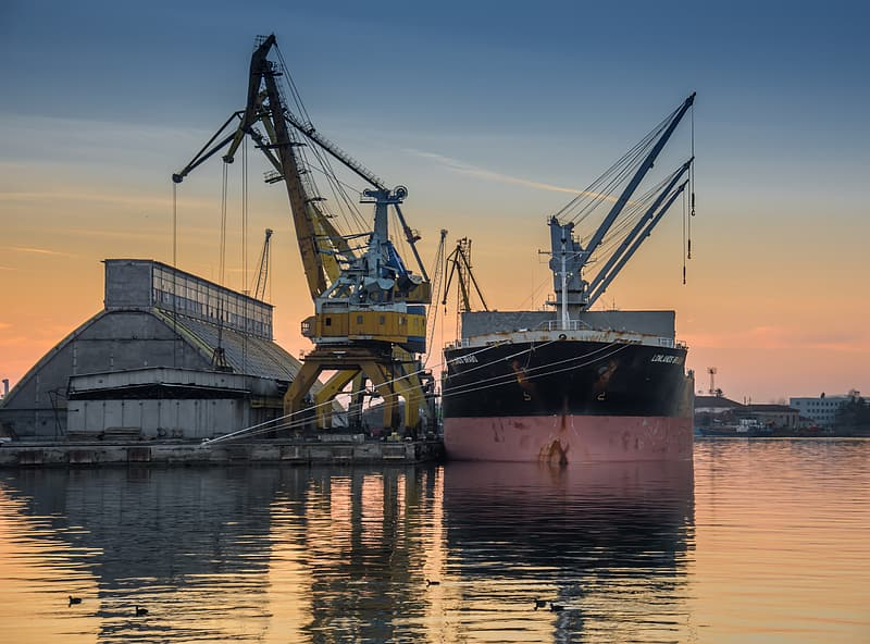 Two yellow and gray heavy equipments on calm water during golden hour