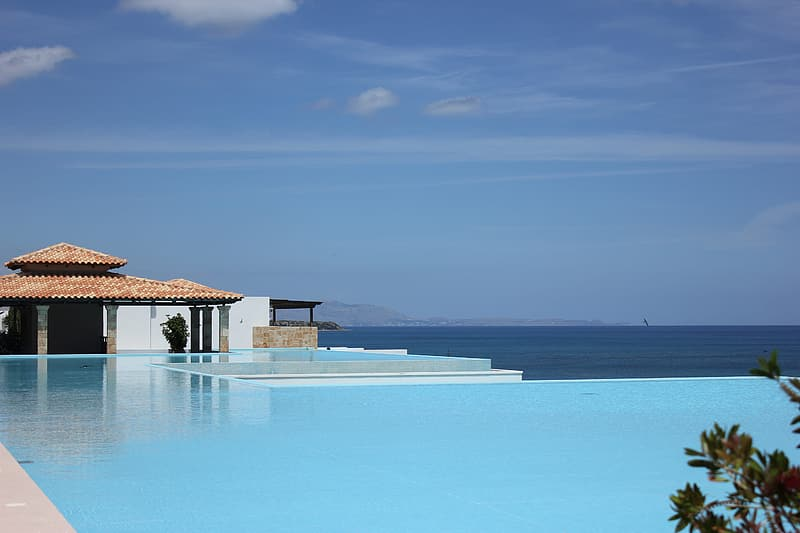 Landscape photography of blue swimming pool with over-view of sea at daytime